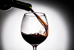 Red wine being poured from bottle in wine glass Stock Images