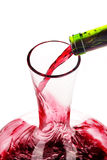 Red wine being poured in a decanter. Selective focus Royalty Free Stock Image