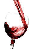 Red wine being poured into glas. White background Royalty Free Stock Image