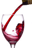 Red wine being poured into a glass. From a bottle, white background Royalty Free Stock Photography