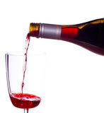 Red wine being poured into glass. Red or rose wine being poured from screw top wine bottle into an elegant glass and isolated against white Royalty Free Stock Images