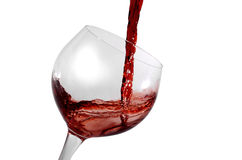 Red wine being poured in glass. Red wine being poured in a tilted wine glass isolation on white Royalty Free Stock Images