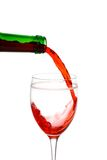 Red wine being poured into a glass. Isolated red wine being poured into a glass on a white background Royalty Free Stock Images