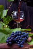 Red wine is being poured into the glass. A bunch of grapes next to it royalty free stock photos
