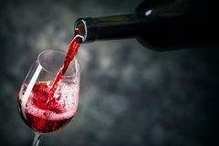 Red wine is being poured into glass. Shot against dark background Royalty Free Stock Photography