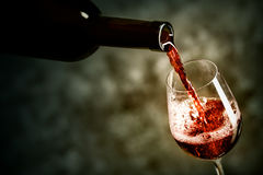 Red wine is being poured into the glass. Shot against dark background Stock Photo