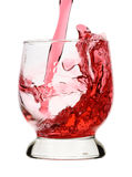 Red wine is being poured into glass, small splash Stock Images