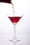 Red wine being poured into glass. Red wine being poured into wine glass on white background Stock Photography