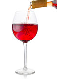 Red wine being poured into glass. Red wine being poured into wine glass on white background Stock Photos