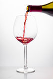 Red wine being poured into glass on white background. Red wine being poured into wine glass on white background Royalty Free Stock Images