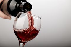 Red wine being poured into wine glass on white background stock photography