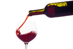 Red wine being poured into a wine glass. In a glass of red wine is lively empties. red wine in a wine glass Royalty Free Stock Photography