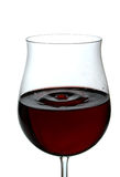 Red wine being poured into a wine glass. White background of a drop sparks of red wine Royalty Free Stock Photos