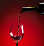 Red wine being poured into wine glass. On red background Royalty Free Stock Images
