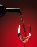 Red wine being poured into wine glass. On red background Stock Images