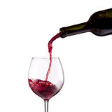Red wine being poured into wine glass. On white background Royalty Free Stock Photography