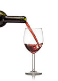 Red wine being poured into wine glass. On white background Stock Images