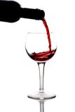 Red wine being pured into a wine glass. Isolated on white royalty free stock images