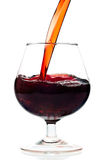 Red wine being served into a glass cup on a white Stock Photos