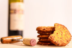 Red Wine and Biscuits. An open bottle of wine with a stack of biscuits and a corkscrew Royalty Free Stock Photos