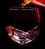 Red wine on black. Red wine pouring into a wine glass isolated on black background Stock Photos