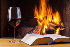 Red wine and book at cozy fireplace