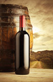 Red wine bottle. And wodden barrel, vineyard on background Stock Photography