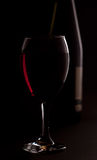 Red wine with bottle in background Royalty Free Stock Photography
