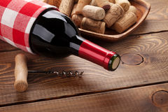 Red wine bottle, bowl with corks and corkscrew Royalty Free Stock Photos