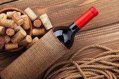 Red wine bottle and bowl with corks Royalty Free Stock Photos