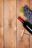 Red wine bottle and bunch of red grapes Stock Image