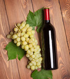 Red wine bottle and bunch of white grapes Stock Photos