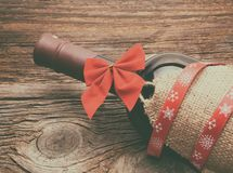Red wine, bottle and christmas ornaments. On wooden background Royalty Free Stock Image