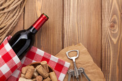 Red wine bottle, corks and corkscrew over wooden table backgroun Royalty Free Stock Photography
