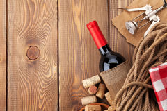 Red wine bottle, corks and corkscrew over wooden table backgroun Stock Photos