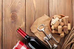 Red wine bottle, corks and corkscrew over wooden table backgroun Royalty Free Stock Photos
