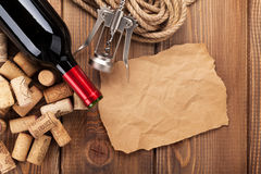 Red wine bottle, corks and corkscrew over wooden table backgroun Royalty Free Stock Image