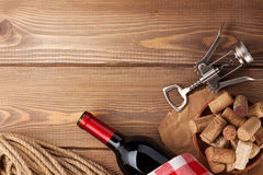 Red wine bottle, corks and corkscrew over wooden table backgroun Stock Image