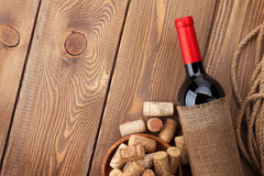 Red wine bottle and corks over wooden table background Stock Image