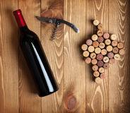 Red wine bottle, corkscrew and grape shaped corks Stock Photography