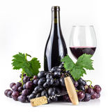 Red wine bottle, corkscrew, wineglass and grapes. Royalty Free Stock Photo