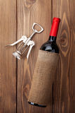 Red wine bottle and corkscrew Stock Images