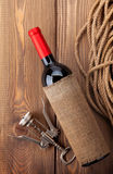 Red wine bottle and corkscrew on wooden table Royalty Free Stock Image