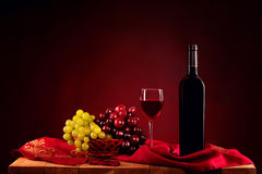 Red wine bottle decor with grapes. Black wine bottle, a glass of red wine, white and red grapes on a black and red background Stock Images