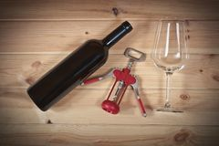 Red wine bottle, empty wine glass and corkscrew. On wooden  background Royalty Free Stock Photos