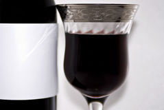 Red wine bottle and a fancy glass - closeup Stock Images