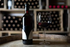 Red wine bottle with a filled wineglass on a barrel in a cellar. Switzerland stock image