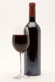 Red wine bottle with filled wineglass in front. On a white background stock image