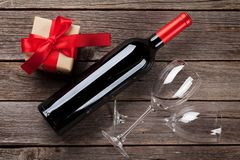 Red wine bottle and gift box. On wooden table. Valentine`s day greeting card. Top view Stock Photo