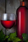 Red Wine Bottle Glass. A close up of a bottle and glass of red wine with a rustic wood background Royalty Free Stock Images